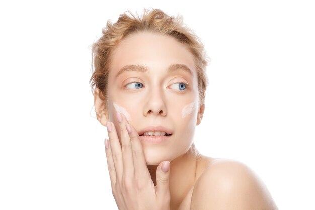 Belle femme blonde à la peau éclatante appliquant la crème pour le visage avec les doigts isolés sur blanc