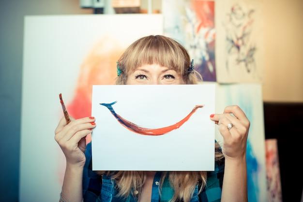Belle femme blonde peintre souriante