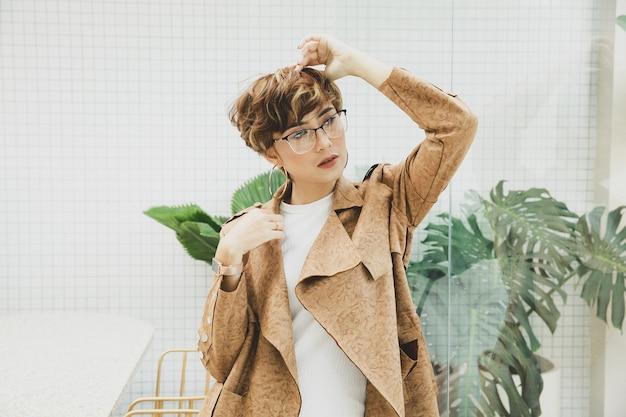 Belle femme blonde portant des lunettes et un manteau marron