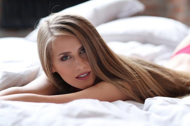 Belle femme blonde posant en sous-vêtements rouges sur le lit