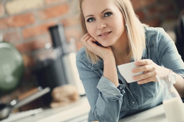 Belle femme blonde posant avec une tasse de café