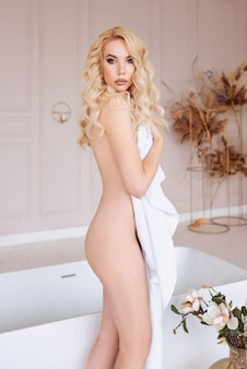 Belle femme blonde de race blanche avec une serviette dans la salle de bain