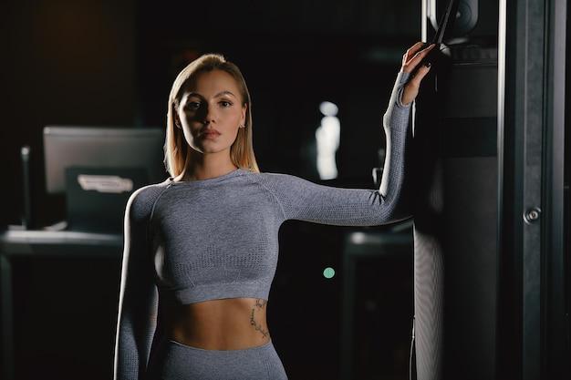 Belle femme blonde de remise en forme se tient près de l'appareil d'entraînement et pose