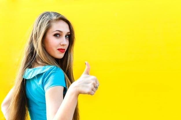 Belle femme blonde en robe bleue montrant le doigt vers le haut.