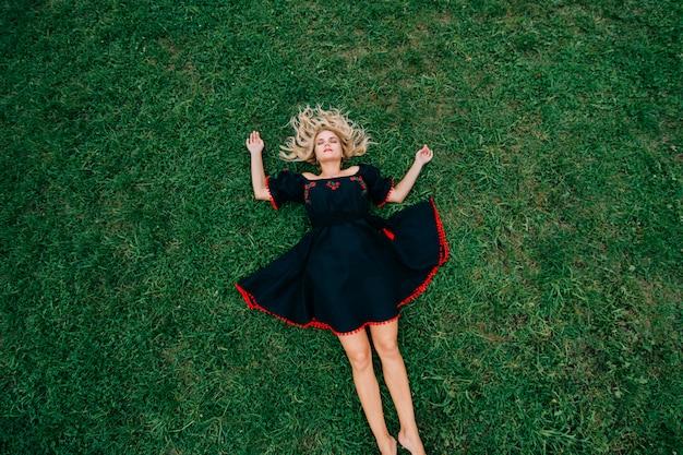 Belle femme blonde en robe de lin ethnique noir couché sur l'herbe verte.