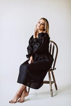 Belle femme blonde en robe de lin noir. mode ethnique, tissu naturel. mise au point sélective douce.