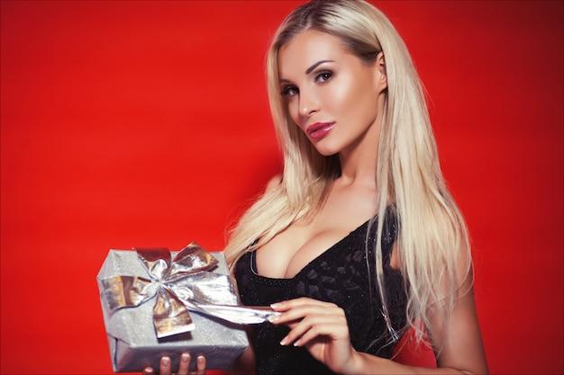 Belle femme blonde en robe noire avec une boîte cadeau sur le fond rouge isolé