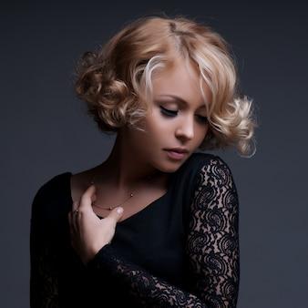 Belle femme blonde avec une robe noire élégante.