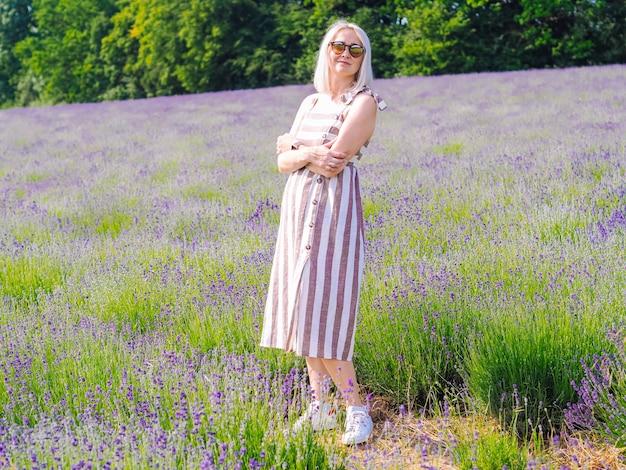 Belle femme blonde en robe s'asseoir entre les champs de lavande en provence. champs de lavande violette fleurissant dans la lumière du soleil d'été. paysage de mer de fleurs lilas. bouquet de fleurs parfumées de provence française