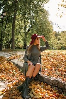 Belle femme blonde en robe en tricot gris et chapeau rouge assis dans le parc en automne