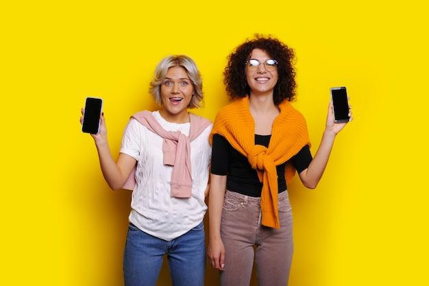 Belle femme blonde et sa belle soeur bouclée regardant la caméra en riant tout en annonçant leur smartphone isolé sur le mur jaune du studio.