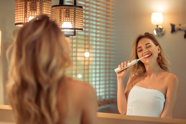 Belle femme blonde se brosser les dents à l'aide d'une brosse à dents électrique s'amuser.