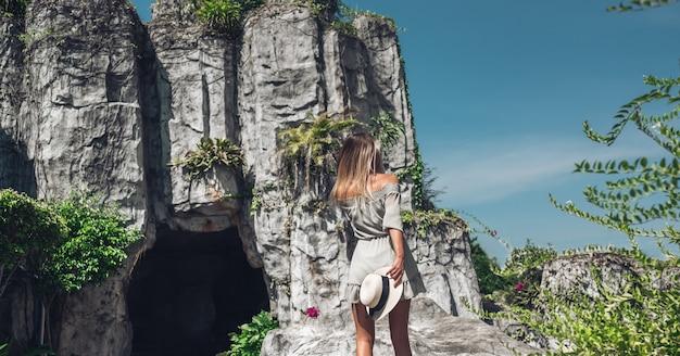 Belle femme blonde se promène sur le territoire d'un hôtel tropical de luxe avec une grotte en pierre naturelle en chine.