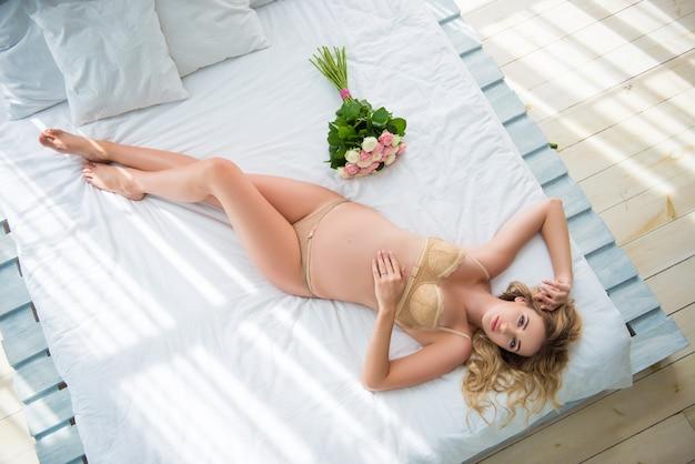 Belle femme blonde se trouve en lingerie sur le lit avec un bouquet de fleurs roses. parfum délicat et féminité.