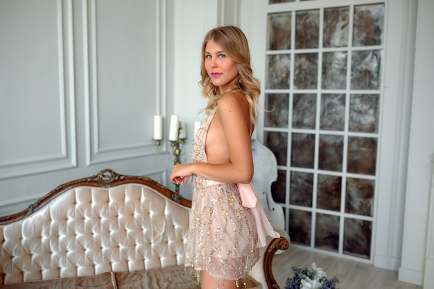Belle femme blonde sexy porter une robe courte en or pour la fête sortir siège de cérémonie sur le canapé en arrière-plan intérieur. le concept d'un complexe coûteux et d'une préparation de fête