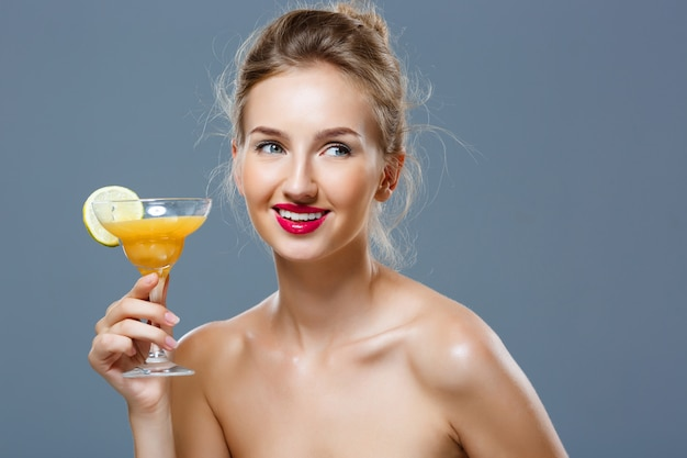 Belle femme blonde souriante, tenant un cocktail