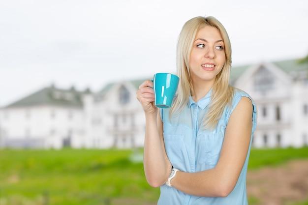 Belle femme blonde tenant une tasse de café