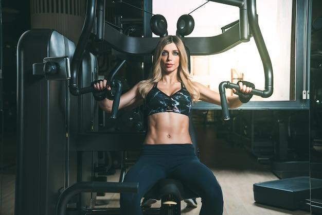 Belle femme blonde travaillant dans la machine de poitrine de gym