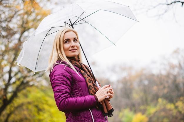 Belle femme blonde en veste et écharpe pourpre brillant tenir un parapluie transparent au fond du parc d'automne, temps pluvieux, marcher à la saison d'automne