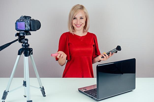 Belle femme blonde vidéoblogueur (blogueur beauté) en robe rouge enregistre un blog vidéo sur les cosmétiques et les pinceaux sur une caméra vidéo devant un ordinateur portable dans un studio.