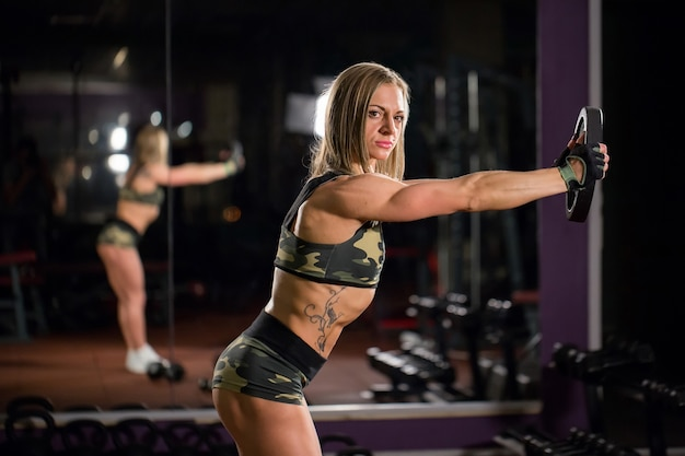 Belle femme bodybuilder avec haltères de levage. fille sportive montrant son corps bien formé. muscles bien développés grâce à la musculation.