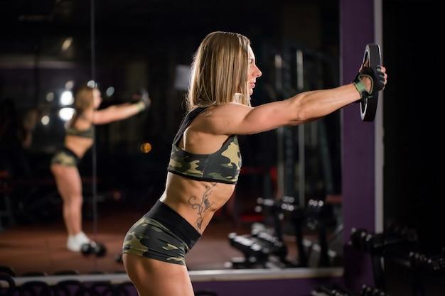 Belle femme bodybuilder avec des haltères de levage