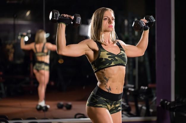 Belle femme bodybuilder avec levage d'haltères. fille sportive montrant son corps bien formé. muscles bien développés par l'entraînement en force.