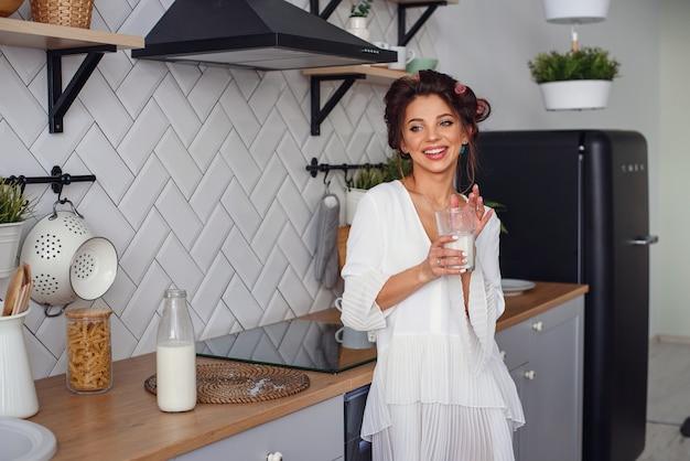 Belle femme boit du lait au petit déjeuner, dans l'élégante cuisine confortable. concept d'alimentation et de régime alimentaire sain.