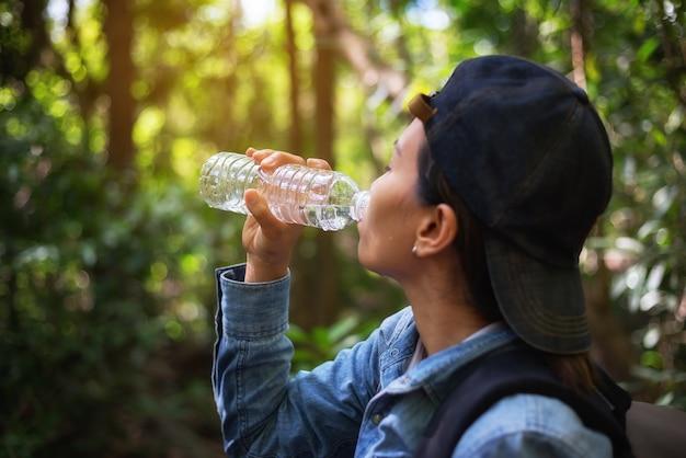 Belle femme boit de l'eau assoiffée pendant la randonnée pour voyager