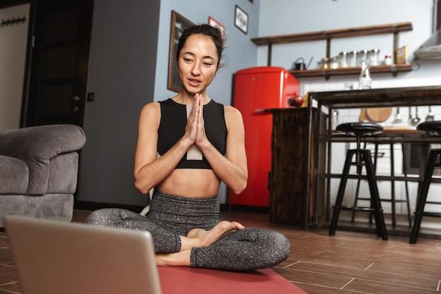 Belle femme en bonne santé, faire des exercices de yoga assis sur un tapis de fitness à la maison, à l'aide d'un ordinateur portable, qui s'étend