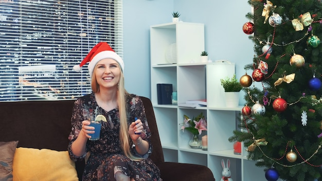 Belle femme en bonnet de noel attend et fête avec émotion la nouvelle année