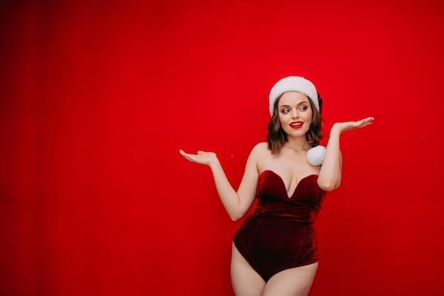 Belle femme en bonnet de noel et body rouge sur fond rouge concept de nouvel an