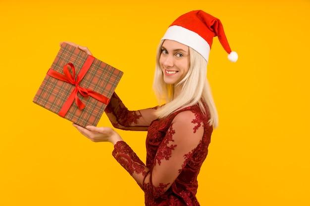 Une belle femme en bonnet de noel et robe rouge tenir en mains des cadeaux sur fond jaune célébration de noël