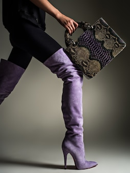 Belle femme en bottes hautes violettes. fille à la mode tient élégant sac en cuir violet. concept élégant glamour. art. modèle marche après le shopping.