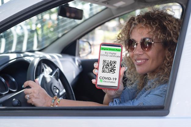 Belle femme bouclée à l'intérieur de la voiture tenant un téléphone portable montrant un certificat de laissez-passer vert numérique