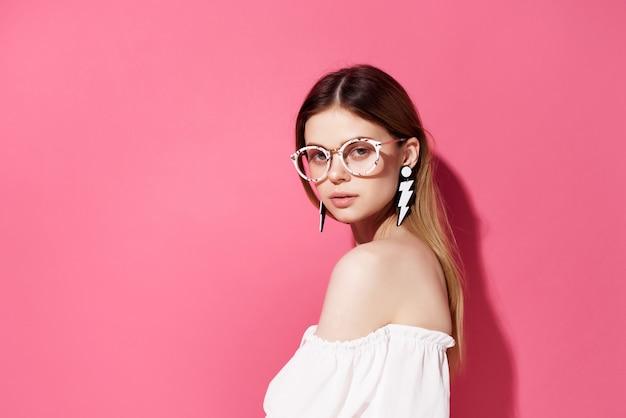 Belle femme avec des boucles d'oreilles lunettes fashion fond isolé