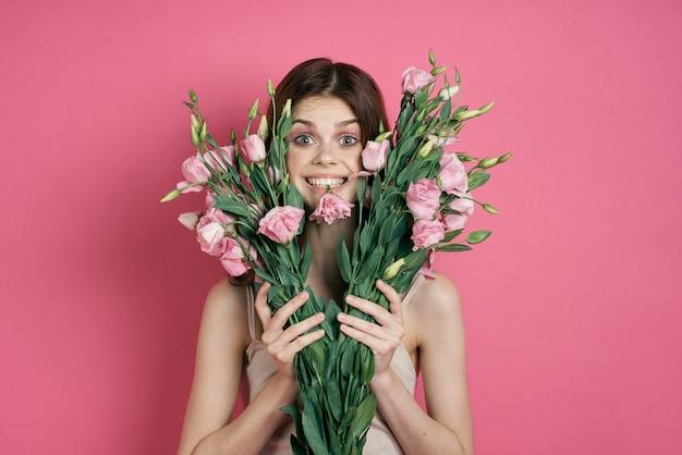 Belle femme avec un bouquet de fleurs sur un mur rose dans un modèle de maquillage robe légère.