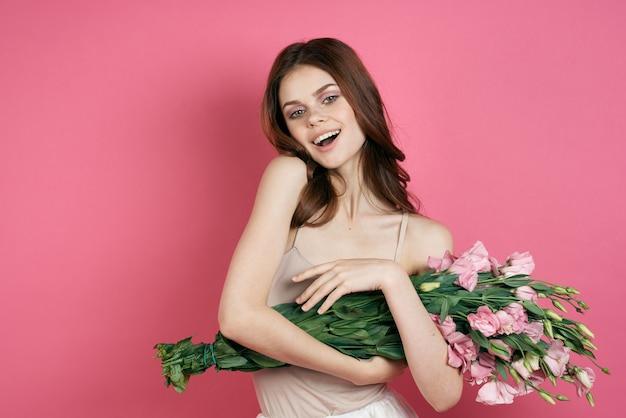 Belle femme avec un bouquet de fleurs sur un rose dans un modèle de maquillage robe légère
