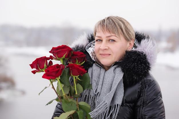Belle femme avec bouquet de roses rouges le jour de la saint-valentin