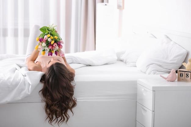 Belle femme avec bouquet de tulipes sur lit à la maison