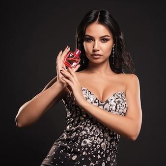 Belle femme avec une bouteille de parfum sur un espace gris.