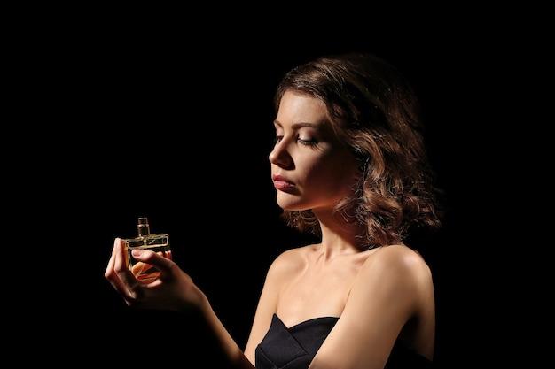 Belle femme avec une bouteille de parfum sur fond noir