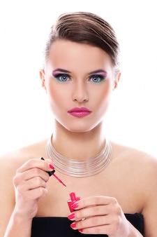 Belle femme avec une bouteille de vernis à ongles rose