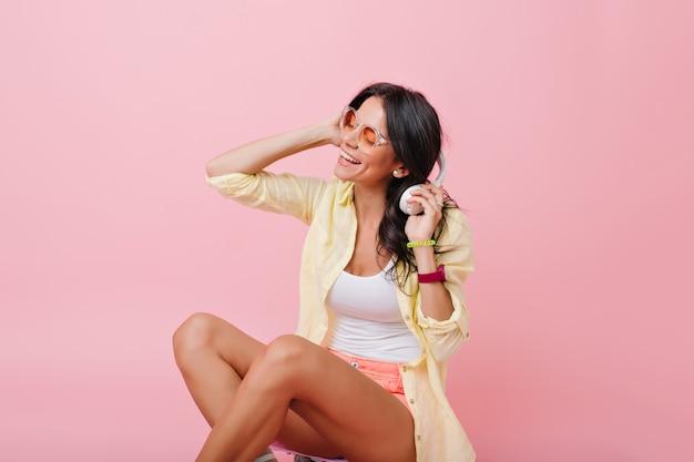 Belle femme bronzée aux cheveux sombres et brillants assis sur le sol et tenant des écouteurs. jolie fille brune à lunettes de soleil et bracelets colorés appréciant la musique.