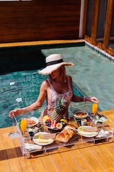 Belle femme bronzée caucasienne en bikini et chapeau de paille avec petit-déjeuner flottant à l'incroyable villa de style bali de luxe à la journée ensoleillée au bord de la piscine, fond tropical.