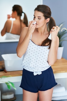 Belle femme brune à l'aide de déodorant dans la salle de bain