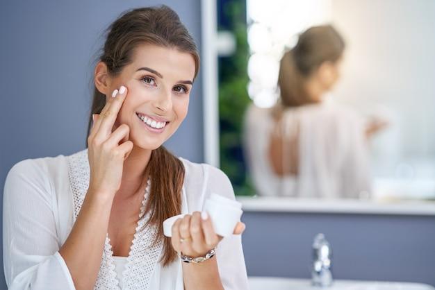 Belle femme brune appliquant une crème pour le visage dans la salle de bain