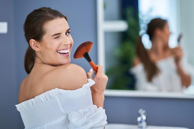 Belle femme brune appliquant mae dans la salle de bain