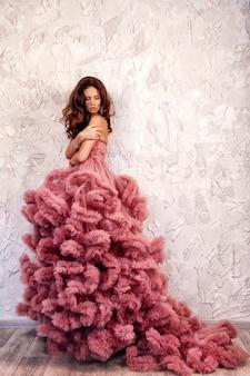 La belle femme brune aux cheveux bouclés, maquillage tendre posant dans une robe de mariée.