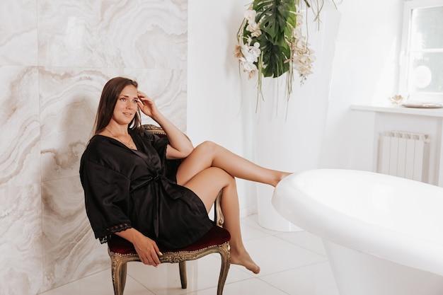Belle femme brune aux cheveux longs dans un déshabillé de soie assis sur le sol près de la salle de bain